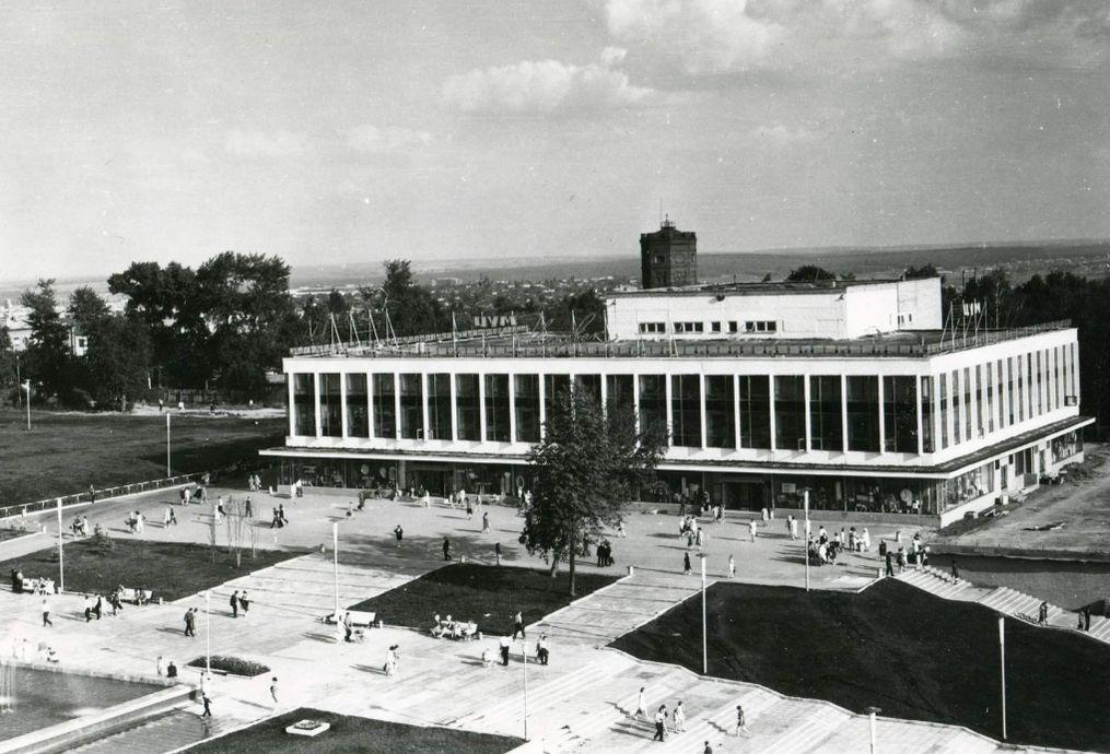 """Центральный универмаг """"Ижевск"""" 1972 года постройки. Слева от ЦУМа стоит деревянный забор с постройками - остатки старой больницы, на горизонте - преобладает деревянная частная застройка. За ЦУМ-ом видна водонапорная башня."""