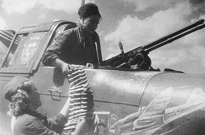 Девушки - оружейницы заряжают пулемет УБТ штурмовика ИЛ-2 капитана Емельяненко В.Б. 1943 год.