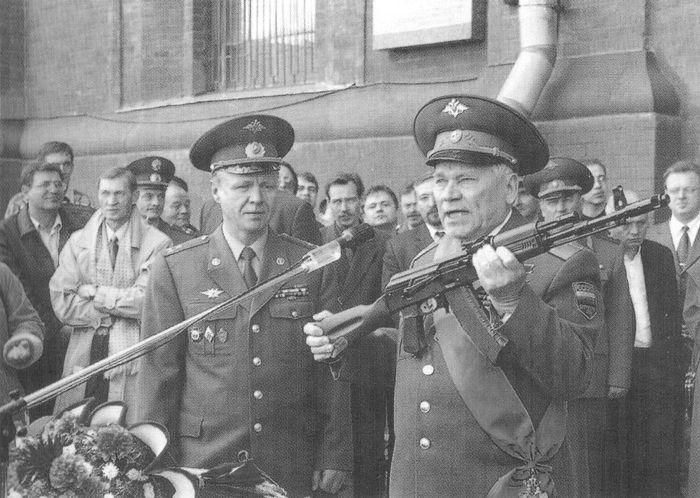 """Генерал-майор М.Т.Калашников передает в дар музею образец пневматической винтовки """"Юнкер"""", разработанной на базе АК-74 (слева - начальник музея полковник В.М.Крылов).  ВИМАИВиВС. 1999г."""