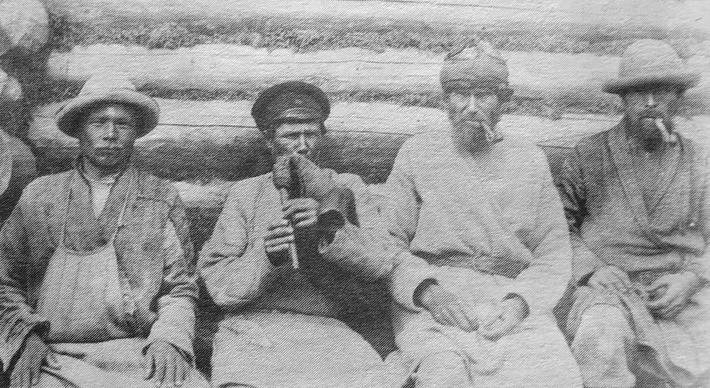 Группа удмуртов в повседневной одежде с трубками. В центре волынщик. Глазовский уезд. 1906 г.